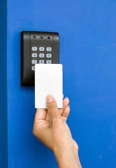 Controle de acesso de porta - jovem mulher segurando um cartão-chave para bloquear e destravar a porta.