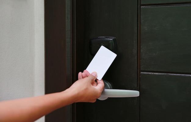 Controle de acesso de porta - jovem mulher segurando um cartão-chave para destravar a porta