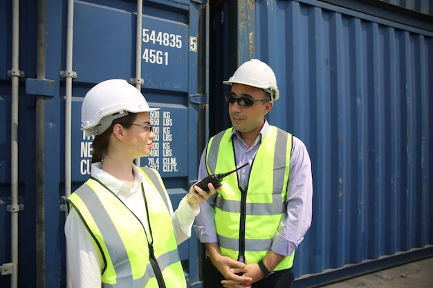 Controle de engenheiro logístico no porto, carregamento de contêineres para exportação de caminhões e conceito logístico de importação