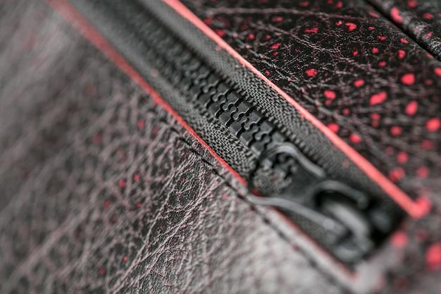Controle deslizante de zíper para uma bolsa de couro vermelho texturizado.