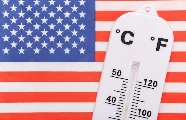 Controle nacional de temperatura ambiente. termômetro do tempo no fundo da bandeira dos eua. conceito de aquecimento global