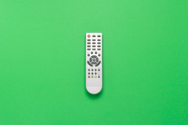 Controle remoto cinza sobre um fundo verde. o conceito de televisão, filmes, programas de tv, esportes, dia e noite. vista plana leiga, superior.