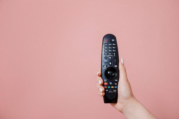 Controle remoto da tv na mão feminina na parede rosa