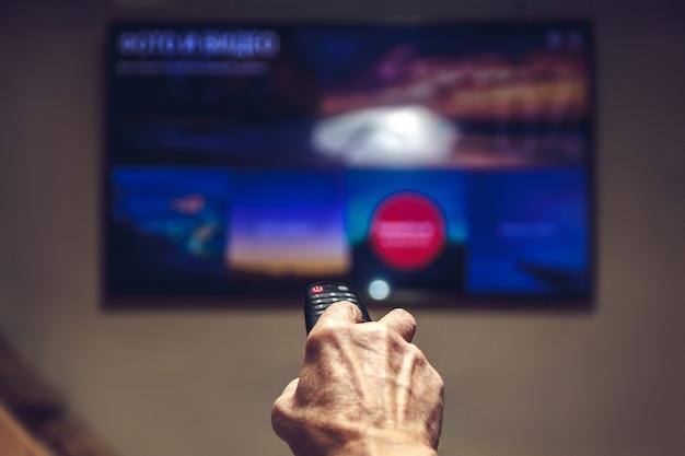 Controle remoto da tv nas mãos de um homem idoso