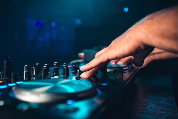 Controles de dj e mixar música em um mixer de música na boate