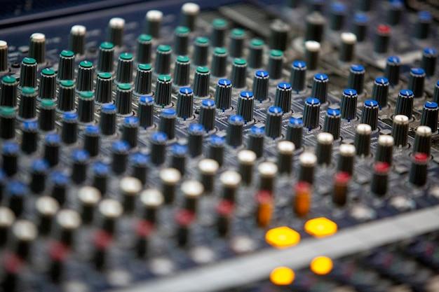 Controles profissionais de mesa de som com vários controles deslizantes de diferentes cores e configurações, em close-up com foco seletivo