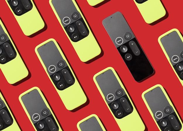 Controles remotos modernos para padrão de tv em fundo vermelho conceito de televisão