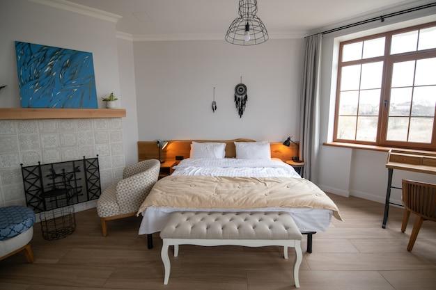 Conveniência. cama grande e confortável com roupa de cama branca em sala de estar bem iluminada com itens de decoração em madeira