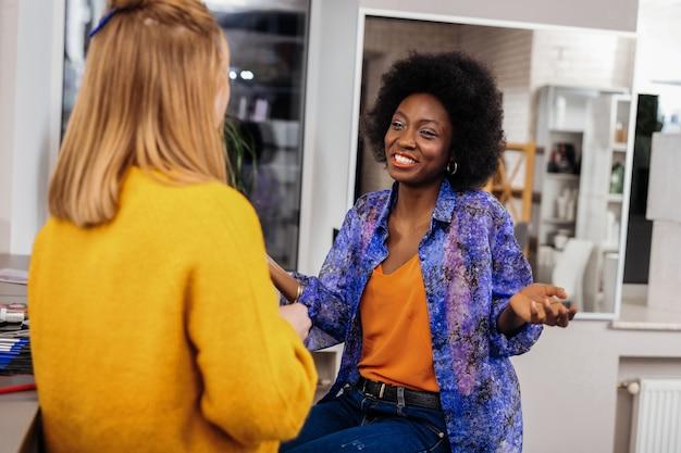 Conversa agradável. estilista linda de pele escura usando uma blusa laranja com uma sensação ótima