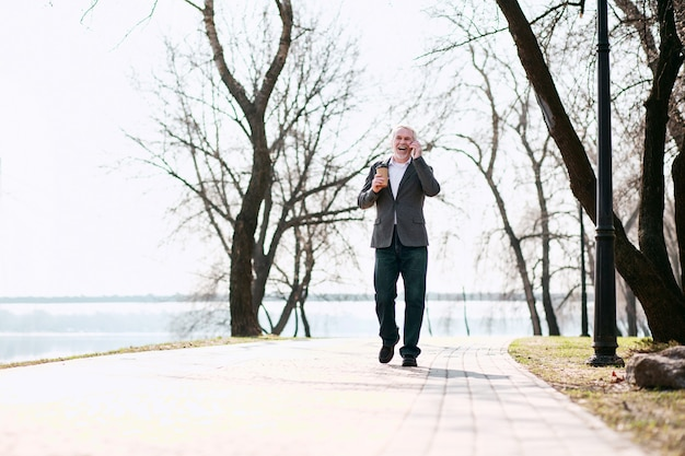 Conversa agradável. homem de negócios gay sênior passeando no parque e falando ao telefone