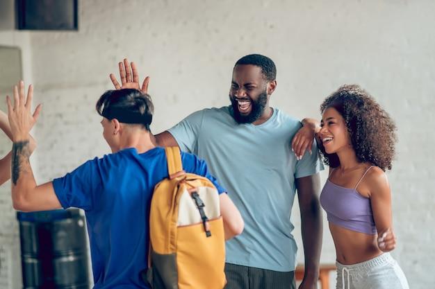 Conversa amigável. jovens rindo felizes em roupas esportivas em pé perto de casa trocando gestos e emoções
