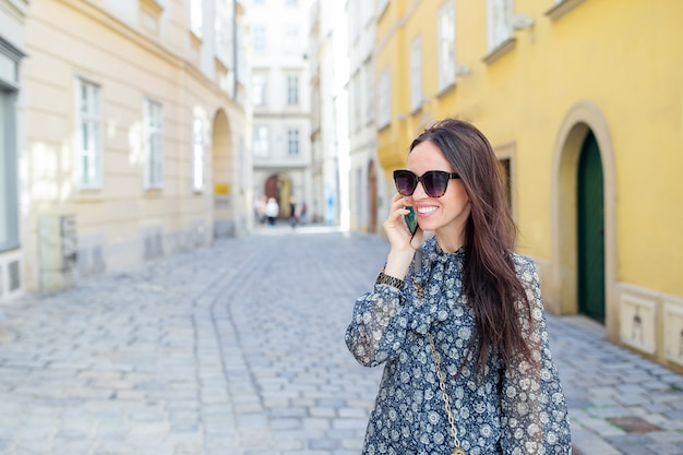 Conversa da mulher por seu smartphone na cidade. jovem atrativos turísticos ao ar livre na cidade italiana