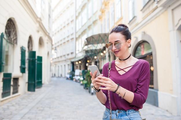 Conversa da mulher por seu smartphone na cidade.