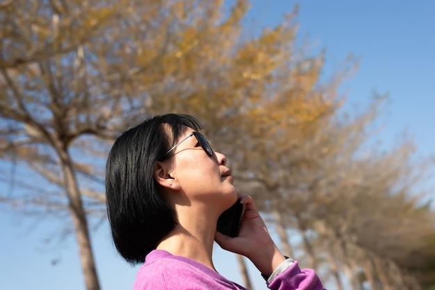 Conversa de beleza asiática madura no celular ao ar livre