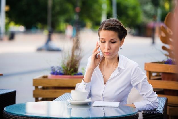 Conversa de bons negócios. empresária jovem alegre, falando no telefone celular e segurando a xícara de café enquanto está sentado ao ar livre