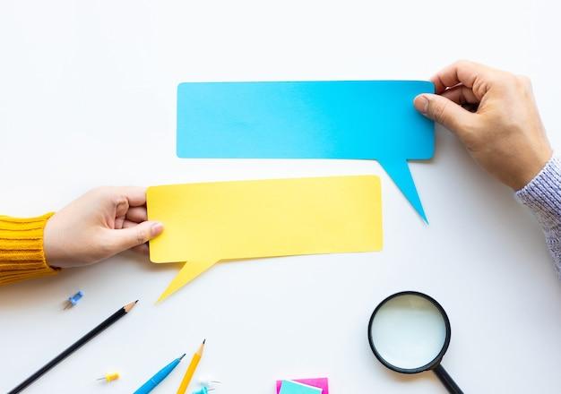 Conversa de conversação ou conceitos de boca a boca com uma mão masculina segurando um papel em branco. copie o espaço