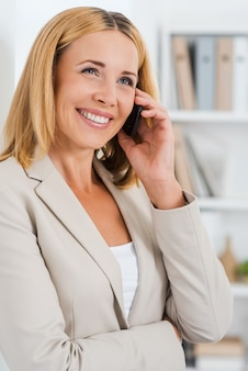 Conversa de negócios. linda mulher de negócios madura falando no celular e sorrindo