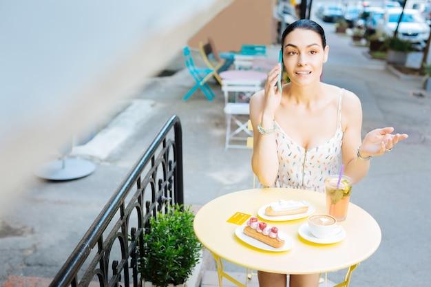 Conversa emocional. mulher jovem emocionalmente falando ao telefone enquanto está sentada ao ar livre à mesa coberta com sobremesas e bebidas