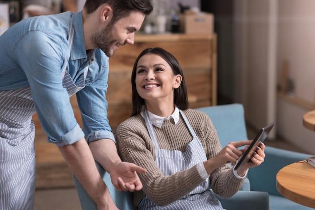 Conversa feliz. bela jovem sentada em uma poltrona e sorrindo enquanto mostra algo em um laptop, seu colega