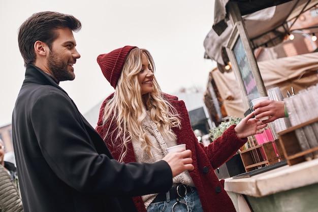 Conversa fiada enquanto espera o café. jovem casal à espera do barista em frente ao balcão de um café moderno