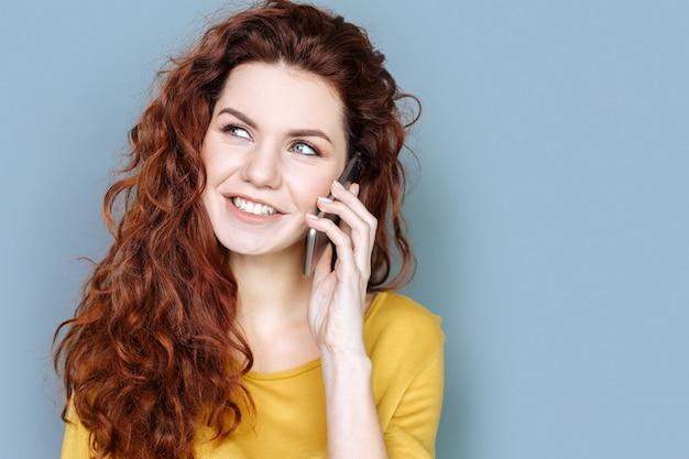 Conversa interessante. mulher simpática e positiva encantada sorrindo e falando ao telefone enquanto está de bom humor
