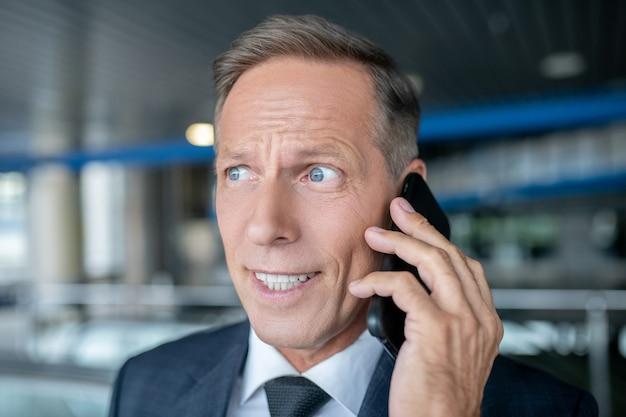 Conversa telefônica. homem adulto atraente de negócios em terno formal e gravata falando no smartphone em um prédio de aeroporto durante o dia