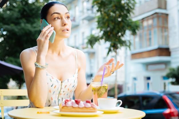Conversa telefônica. jovem atenciosa sentada à mesa ao ar livre com sobremesas à sua frente e conversando ao telefone