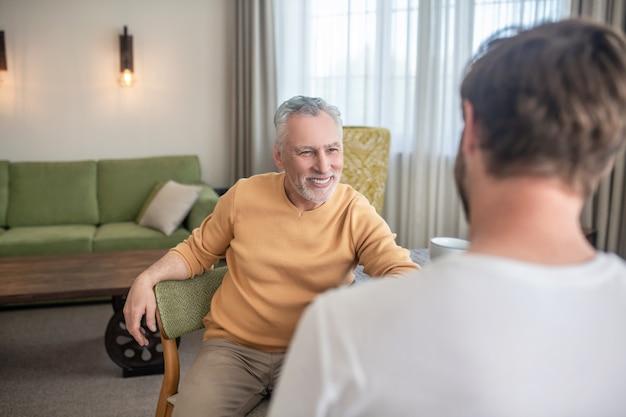 Conversação. dois homens sentados à mesa, tomando chá e conversando