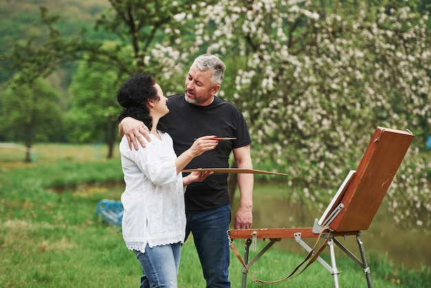 Conversando. casal maduro tem dias de lazer e trabalhando na pintura juntos no parque