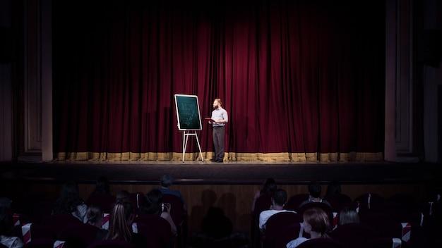 Conversando com alunos. palestrante feminino fazendo apresentação no corredor do workshop. centro de negócios. vista traseira dos participantes na audiência. evento de conferência, treinamento.