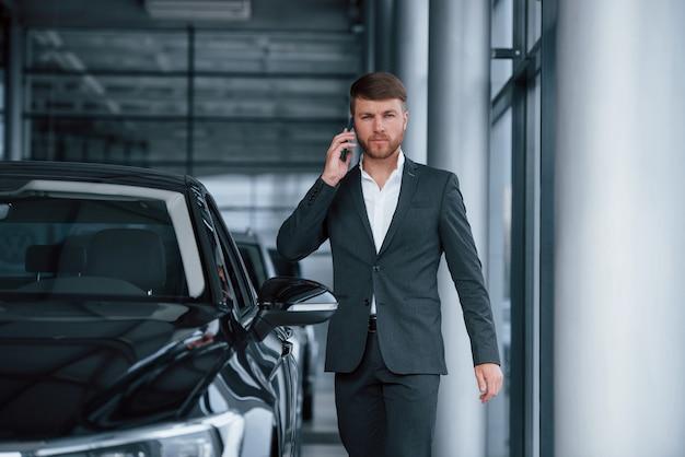 Conversando. homem de negócios barbudo elegante moderno no salão automóvel.