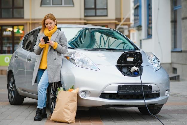 Conversando usando o telefone. mulher na estação de recarga de carros elétricos na hora do dia
