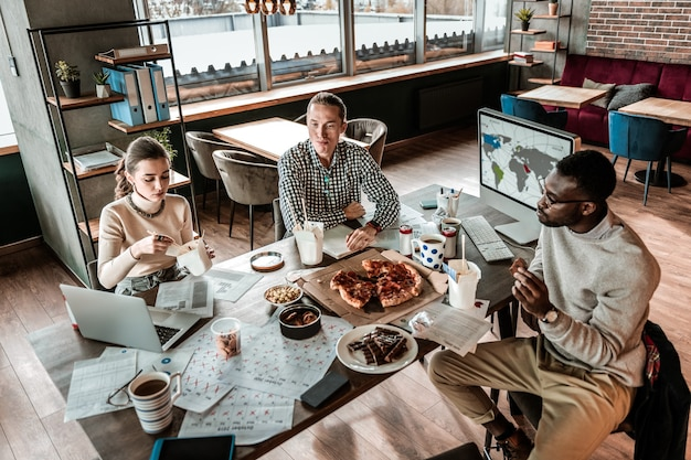 Conversas amigáveis. homem internacional atencioso comendo comida asiática enquanto ouve seus amigos