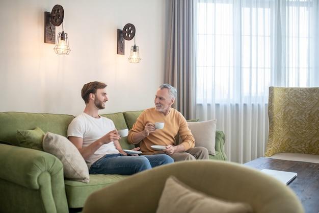 Conversas matinais. dois homens sentados no sofá tomando chá