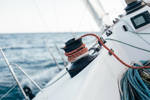 Convés de um veleiro profissional ou iate de corrida durante a competição em um dia ensolarado e ventoso de verão, movendo-se rapidamente através das ondas e da água, com a spinnaker levantada