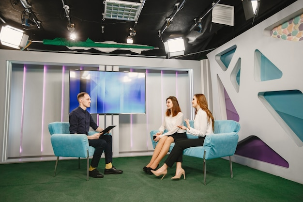 Convidadas do sexo feminino estão sentadas no sofá. entrevista de entrevista de jornalista. show de manhã.