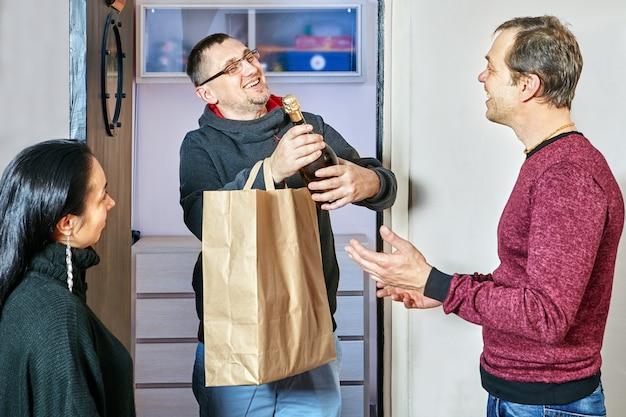 Convidado alegre com garrafa de champanhe chegou à casa do casal de amigos.