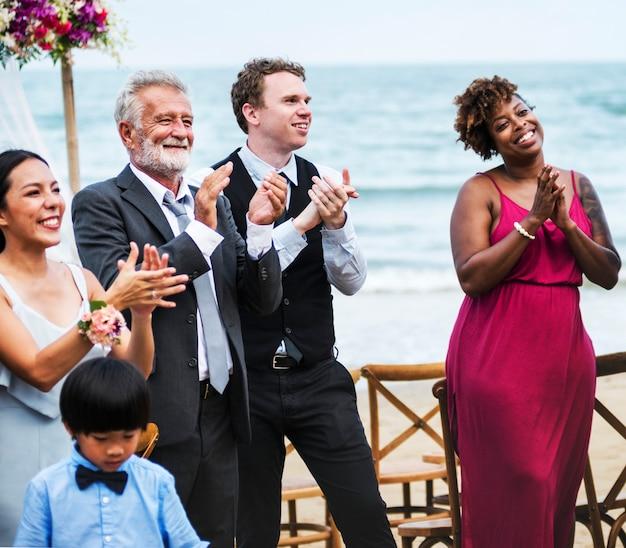Convidados do casamento aplaudindo para a noiva eo noivo