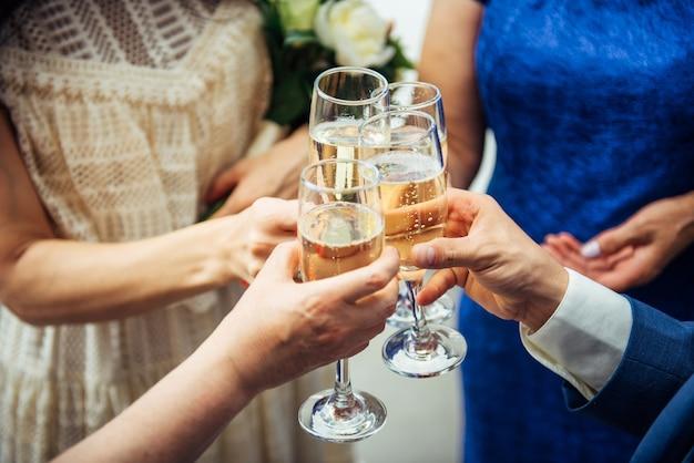 Convidados e parentes de diferentes idades no casamento erguem suas taças com champanhe festivo