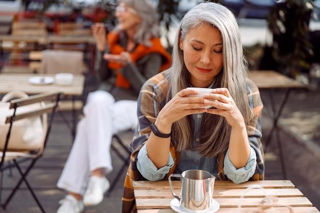 Convidados seniores do café se concentram em uma senhora de cabelos grisalhos segurando um copo de bebida