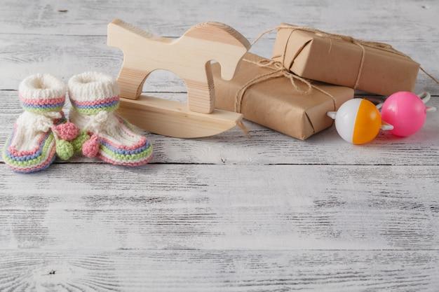 Convite de aniversario. chocalho, cavalo de madeira e botas de malha para o recém-nascido