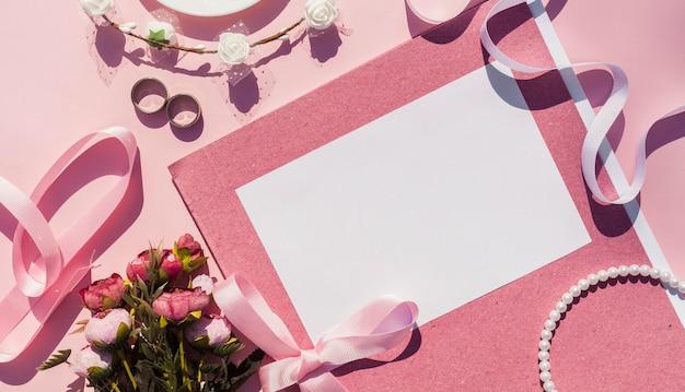 Convite de casamento rosa ao lado de itens de casamento