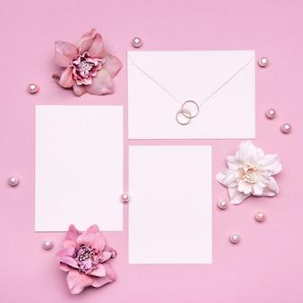 Convite de casamento vista superior com anéis em cima da mesa