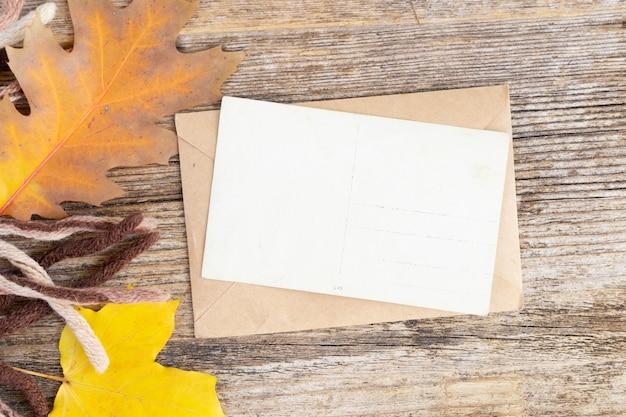 Convite de outono de cartão branco e folhas em fundo de outono