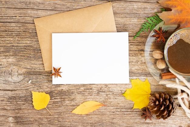 Convite de outono de cartão branco, folhas e café em fundo de madeira de outono