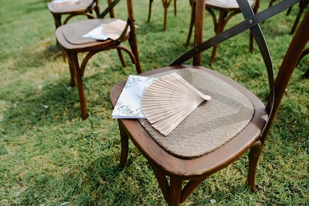 Convite do convidado, ventilador de mão na cadeira elegante antiquada marrom ao ar livre