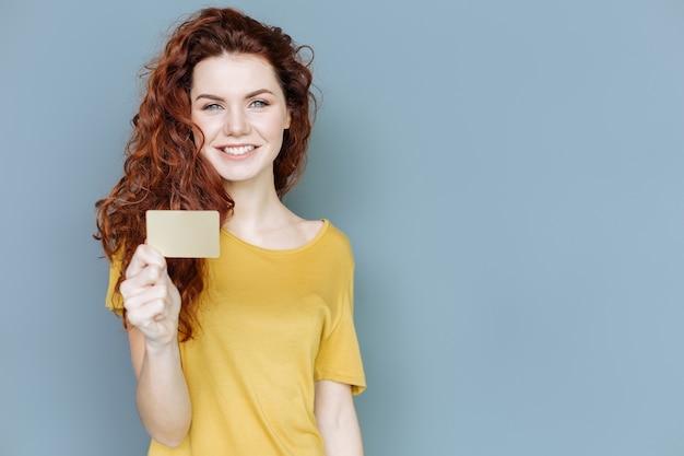 Convite. mulher alegre e positiva sorrindo e segurando um pedaço de papel enquanto olha para você
