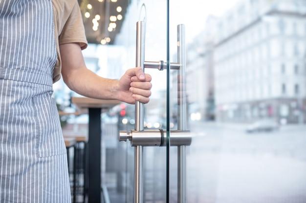 Convite para entrar. mão de homem segurando firmemente para limpar a maçaneta da porta de vidro dentro do café, sem rosto visível