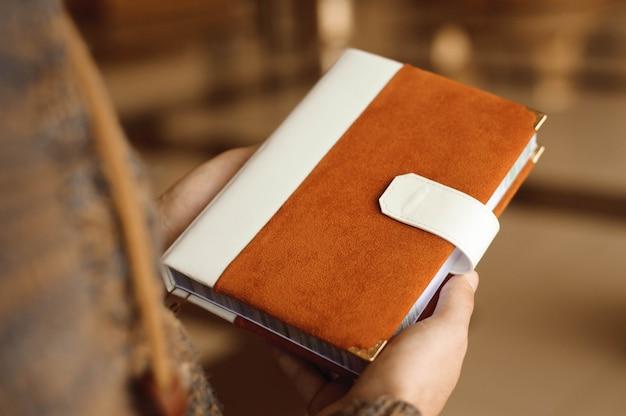 Convites, bloco de notas, caderno artesanal nas mãos.