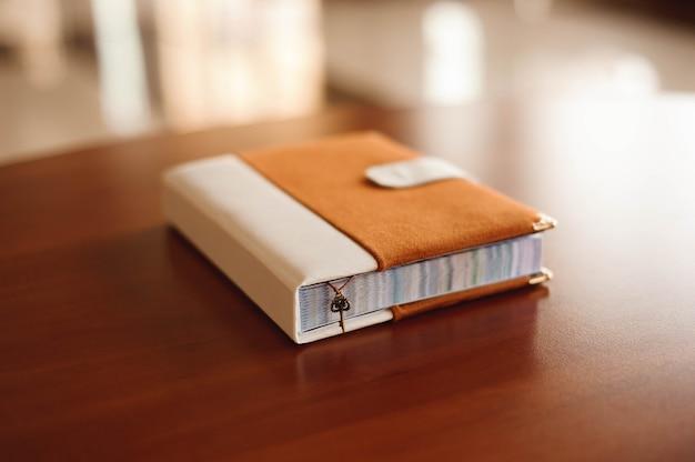 Convites, bloco de notas, caderno feito à mão sobre a mesa de madeira.